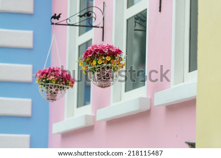 baskets of flowers hanging on a building - stock photo