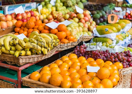 Baskets of neatly arranged fruit at farmers market.  Various display baskets of neatly arranged fruit for sale on street market in Madeira Portugal - stock photo