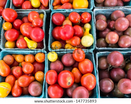 Baskets with a variety of heirloom cherry tomatoes at farm market. - stock photo