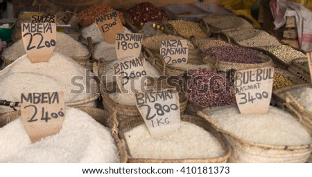 baskets with different rice sorts and price labels on market in zanzibar, tanzania - stock photo