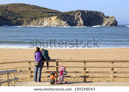 BASQUE COUNTRY, SPAIN - DECEMBER 08, 2011: Lovely view of a mother and daughter together watching the beach in winter in the Basque Country, Spain on Dec 08, 2011 - stock photo