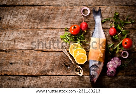 Bass fish and ingredient on wooden background with blank space  - stock photo