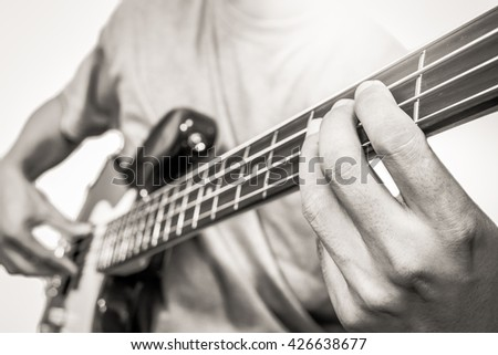 bass player isolated on white, shallow dept of field / focus on left hand. vintage BW filter - stock photo