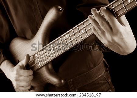 bassist playing funk slap on bass guitar, sepia image - stock photo