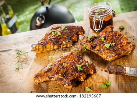 Basting and seasoning ribs for the BBQ with three portions of meat laid out on a wooden picnic table in a summer garden with a jar of basting sauce and herbs - stock photo