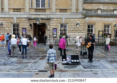BATH - AUG 9: An unidentified musician performs in the courtyard of Bath Abbey and Roman Baths on Aug 9, 2014 in Bath, UK. Bath is a UNESCO world heritage city and popular tourist destination. - stock photo