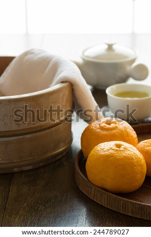 Bath bucket, towel, and fruits of yuzu in preparation to a traditional yuzu bath at onsen (yuzuyu and yuzuburo) on a day of winter solstice (old Japanese custom). Served with a cup of refreshing tea.  - stock photo