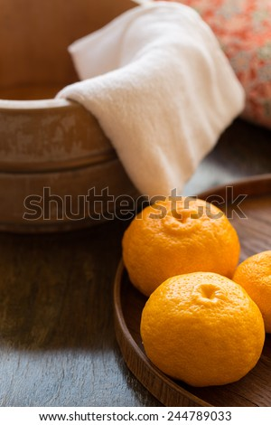 Bath bucket, towel, and fruits of yuzu in preparation to a traditional yuzu bath at onsen (yuzuyu and yuzuburo) on a day of winter solstice, a Japanese custom that dates to early 18th century. - stock photo