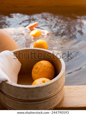 Bath bucket with fruits of yuzu during traditional yuzu bathing at Japanese onsen. This bath also known as yuzuyu and yuzuburo, taken during winter solstice, a custom that dates to early 18th century. - stock photo