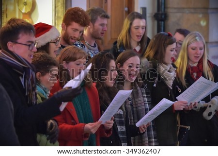 BATH - DEC 9: People sing carols at the Christmas Market in the streets surrounding Bath Abbey on Dec 9, 2015 in Bath, UK. The market is held annually in the historic Unesco World Heritage City. - stock photo