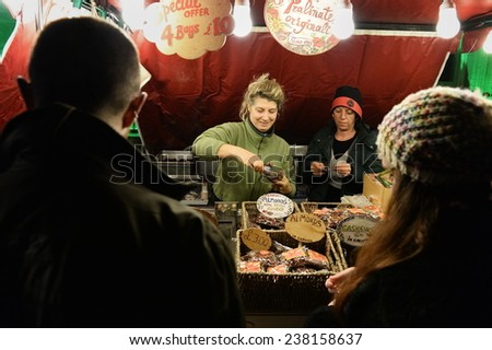 BATH - NOV 30: A vendor serves customers at a Christmas Market stall in the streets surrounding Bath Abbey on Nov 30, 2014 in Bath, UK. The market has become an annual fixture for the historic city.  - stock photo