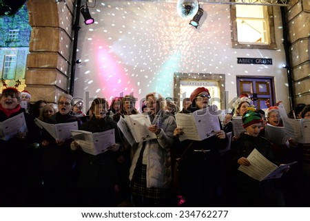BATH - NOV 30: People sing carols at the Christmas Market in the streets surrounding Bath Abbey on Nov 30, 2014 in Bath, UK. The market is held annually in the historic Unesco World Heritage City. - stock photo