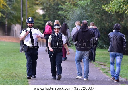 BATH - OCT 20: Police patrol Victoria Park on Oct 20, 2015 in Bath, UK. Despite calls for great protection to police, regular British police officers continue to not carry firearms.  - stock photo