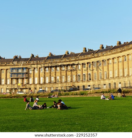 BATH - SEP 12: People gather in the warm evening sun in Victoria Park below the landmark Royal Crescent on Sep 12, 2014 in Bath, UK. Bath is a UNESCO World Heritage city with 4.5mln visitors a year. - stock photo