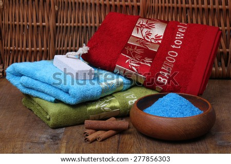 Bath towels of different colors in wicker basket on wooden table - stock photo