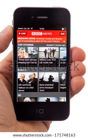 BATH, UK - JANUARY 16, 2014: A hand holding an Apple iPhone 4s displaying the front page of the BBC News App, against a white background. The app can be used to read the latest stories or watch video. - stock photo