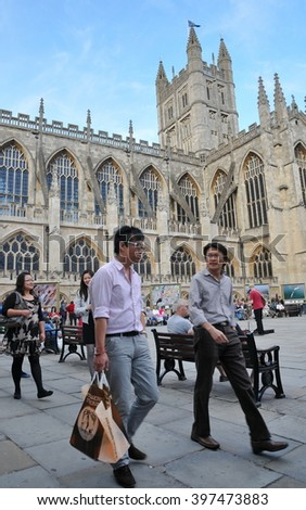 Bath, UK - September 12, 2010: Tourists and locals walk through the courtyard of the historic Bath Abbey and Roman Baths. The picturesque Somerset city receives over 4 million visitors each year. - stock photo