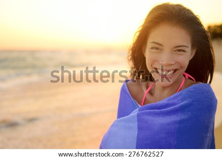 Bathing beach woman with towel happy portrait. Young pretty mixed race Asian Caucasian girl wrapped in towel standing in beach sunset. Smiling happy enjoying summer holiday travel vacation. Hawaii. - stock photo