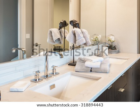Bathroom detail in new luxury home: vanity with cabinet. Dual sinks and counter decorated with towels - stock photo