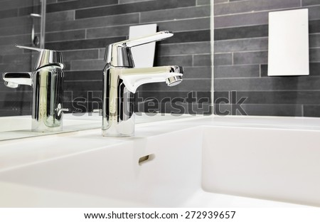 Bathroom environment with a brick wall, chrome faucet, a soap dispenser and a white, square sink. - stock photo