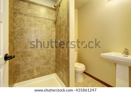 Bathroom interior design. View of washbasin stand, toilet and open shower with tile wall trim - stock photo