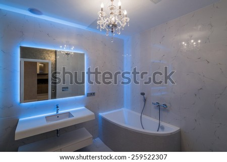 Bathroom interior with a bath and a mirror with a soft blue backlight - stock photo