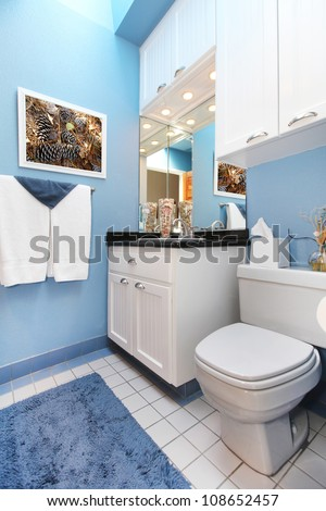 Bathroom interior with blue walls and white cabinets. - stock photo