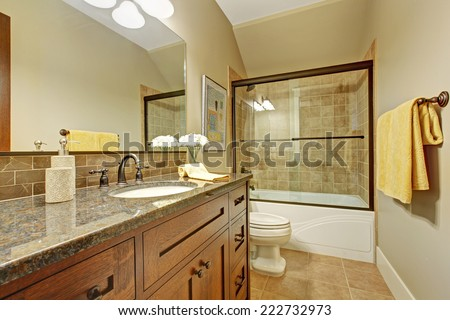 Bathroom interior with screened bath tub, wooden vanity cabinet with drawers and granite top - stock photo