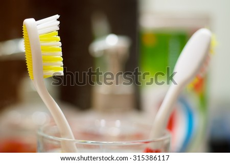 Bathroom interior with two toothbrushes in the foreground. Closeup with shallow DOF. - stock photo