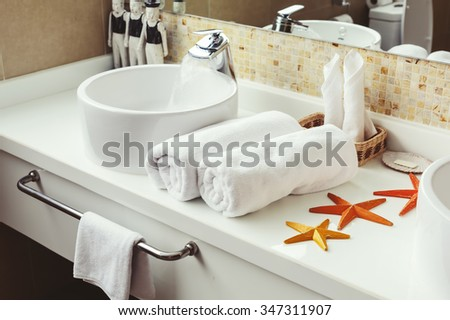 Bathroom Luxury interior. White towels, tropical decor. Water flow from tap - stock photo