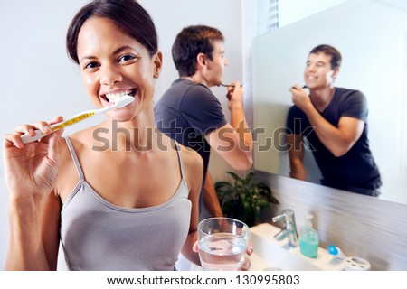 Bathroom routine for happy young couple brushing teeth and shaving in mirror - stock photo