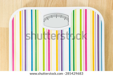 Bathroom scale with clean dial with lines no numbers on wooden floor - stock photo