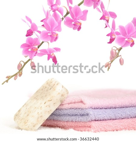 Bathroom set with three towels, a bar of natural soap and a decorative pink orchid - stock photo