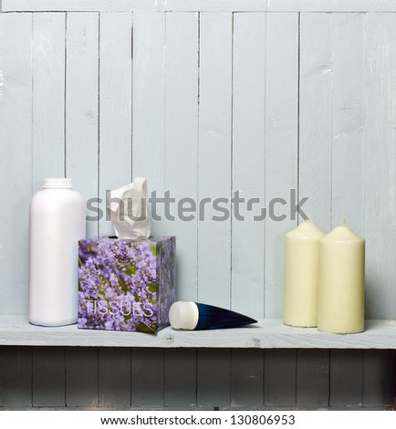 bathroom shelf; photographed against rustic wall; with cream, powder, tissues; good copy-space - stock photo