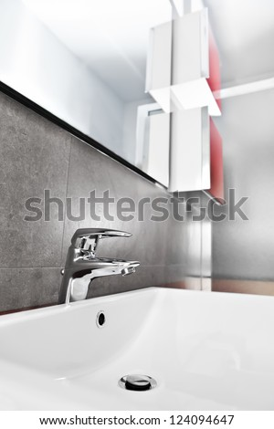 Bathroom white porcelain sink closeup with red furniture - stock photo