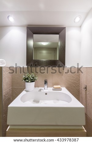 Bathroom with glossy white and brown tiles, new basin and mirror - stock photo