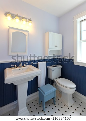 Bathroom with sink and toilet with blue walls and tile floor. - stock photo