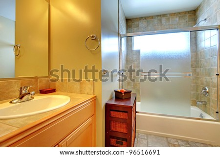 Bathroom with tub behind modern glass, stone tile, and white sink in a wood cabinet. - stock photo