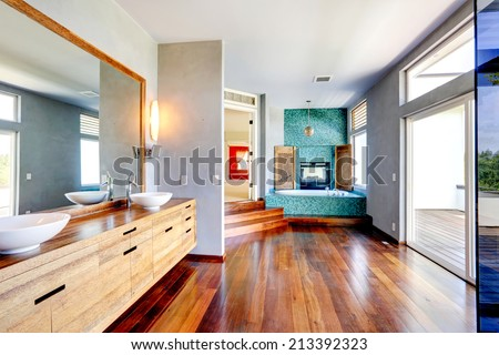 Bathroom with turquoise tile trim and fireplace. View of wooden cabinet with vessel sinks and mirror - stock photo
