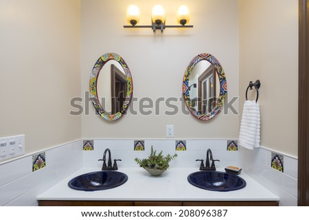 Bathroom with vanity with double sink, tiles ornamented with counter top with black sinks and oval shaped mirrors  - stock photo