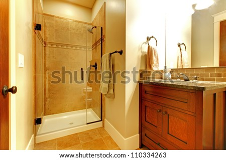 Bathroom with wood cabinet and tile shower with golden tone. - stock photo