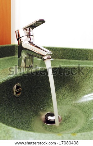 Bathtub faucet on the sink with running water - stock photo