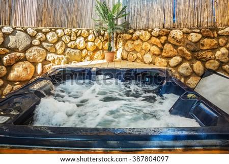 Bathtub -  jacuzzi in garden. Water in bathtub rages - stock photo