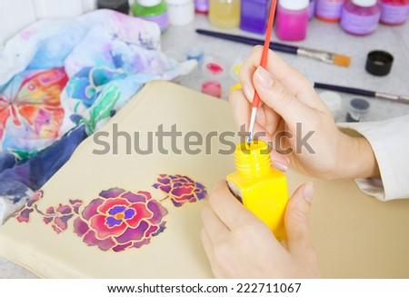 Batik process: artist paints on fabric, Batik-making. An artist paint the floral motif on a batik fabric - stock photo
