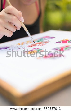 Batik process: woman artist paints on fabric, Batik-making. Artist paint the underwater creatures on a batik fabric. Selective focus, shallow depth of field. (set photo) - stock photo