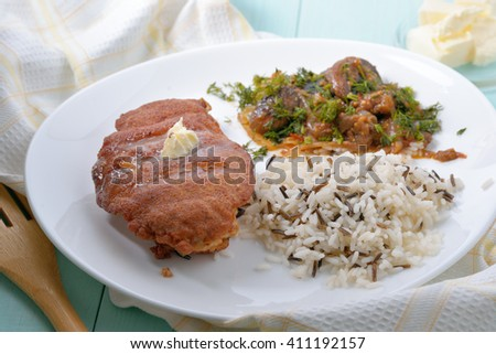 Battered chicken fillet with a side dish of rice and mushrooms. - stock photo