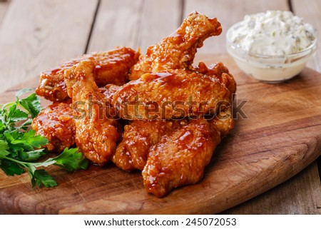 Battered chicken wings in red spicy sauce - stock photo