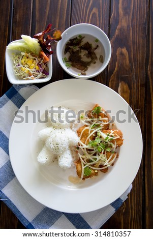 battered fish on a plate with rice on wooden. - stock photo