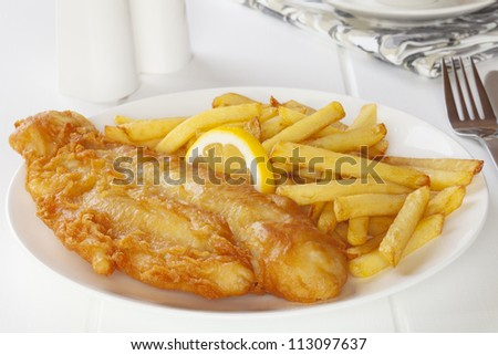 Battered fish with chips in a light, bright setting. - stock photo