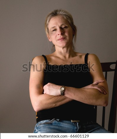 battered woman (bruises on face, throat,arm), looking defiant, strong, ready to take her life back - stock photo